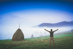 Early morning in a misty mountains. Instagram stylisation. Man with raised hands in a carpathian mountain valley with haystack on a hill. Instagram stylisation Stock Photo