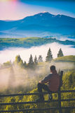Early morning in a misty valley. Instagram stylisation. Man sitting on a wooden fence in a carpathian mountain valley covered with morning fog. Instagram Stock Photography