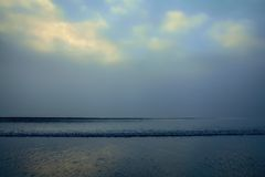 Early morning Ocean. Early morning at an isolated beach, foggy, small patch of blue sky above, gently rolling waves Royalty Free Stock Photo