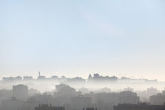 Early morning over the roofs of city, silhouettes of buildings Royalty Free Stock Images