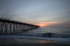 Early Morning at the Pier. The sky lightens in the east as the fishermen cast their lures from the Kure Beach Pier Stock Photos