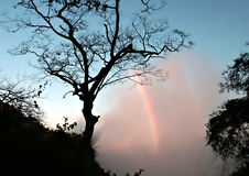 Early morning rainbow on Victoria Falls spray. Zambia Royalty Free Stock Photography