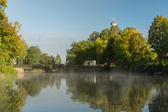 Early morning by a river with mist and autumn colored trees. Beautiful view of trees in autumn colors by a river with mist in early morning sunshine. A church Royalty Free Stock Photo