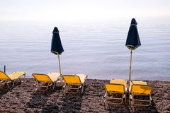 Early morning on sandy beach without people with empty chaise lounges, sun beds, sunshades, summer umbrella parasol, loungers. Early morning on sandy beach royalty free stock images