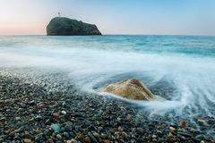 Early morning on a scenic pebbly beach. Stones in the sea on a long exposure Stock Image