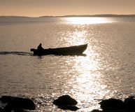 Early morning at sea. Small motorboat plowing through calm water an early morning Stock Images