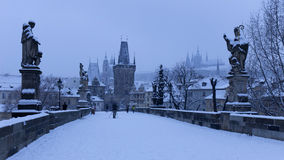 Early Morning snowy Prague Lesser Town with Bridge Tower, Castle and St. Nicholas' Cathedral from Charles Bridge Stock Images
