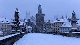 Early Morning snowy Prague Lesser Town with Bridge Tower, Castle and St. Nicholas' Cathedral from Charles Bridge Royalty Free Stock Photo