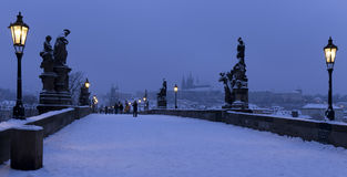 Early Morning snowy Prague Lesser Town  with gothic Castle, Bridge Tower and St. Nicholas' Cathedral from Charles Bridge Stock Photo
