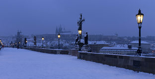 Early Morning snowy Prague Lesser Town  with gothic Castle, Bridge Tower and St. Nicholas' Cathedral from Charles Bridge Royalty Free Stock Photos