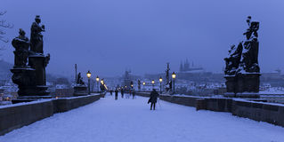 Early Morning snowy Prague Lesser Town  with gothic Castle, Bridge Tower and St. Nicholas' Cathedral from Charles Bridge Royalty Free Stock Image
