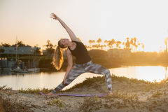 Early morning stretch at beach has blond reaching for the sky. Backlit female Yoga practitioner holding Reverse Warrior pose at sunrise Royalty Free Stock Images