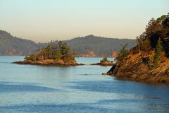 Small Rocky Islet at the Entrance of Otter Bay, North Pender Island, British Columbia. Early morning sun at the entrance of Otter Bay on North Pender Island Stock Photos