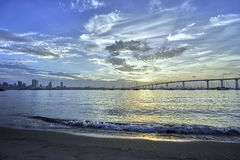 The early morning sun peeks through clouds above the California marine layer haze. View from Dinghy Landing on Coronado Island towards downtown San Diego stock images