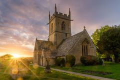 Sun burst over a church in Willersey royalty free stock photography