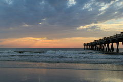 Early morning sunrise at the beach, with fishing pier just beyond Stock Photo