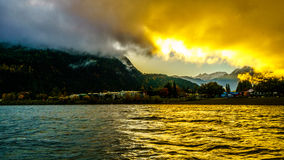 Early Morning Sunrise and Dark Clouds over the town of Harrison Hot Springs Royalty Free Stock Image