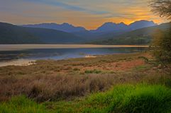 Dawn over lake with blue mountains Royalty Free Stock Images