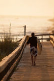 Early Morning Surfer. Surfer heading down to the beach in early morning sunlight Stock Photos