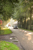 Early morning traffic on country. Country road with traffic, farm, trees and sunbeams at sunrise Royalty Free Stock Photos