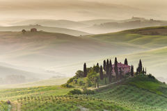 Early morning in Tuscany. Early morning view on farmhouse with hazy hills in the background. Countryside, San Quirico d´Orcia, Tuscany, Italy