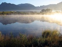 Early morning vapour. Sunlit vapour on the waters of a tranquil rural dam at sunrise Stock Photo