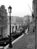 Early morning in Venice. Foggy early morning in Venice: view along a canal, with houses immersed in water, row of boats, poles and lampposts. Black and white, BW Royalty Free Stock Photos