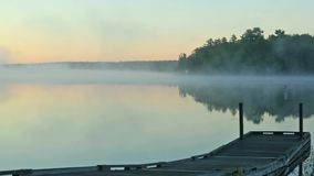 Early morning video of mist over Toddy Pond, Maine. A video of the morning mist over Toddy Pond in East Orland Maine with a small pier in the foreground stock video footage