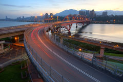 Early morning view of car trails on a curved highway bridge over beautiful Tamsui River in Taipei City,Taiwan. ~ Romantic scenery of Taipei City under dawning Royalty Free Stock Photos