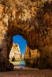 Early morning view through limestone arches on Praia Dos Tres Ir. Maos, Algarve, Portugal Royalty Free Stock Image