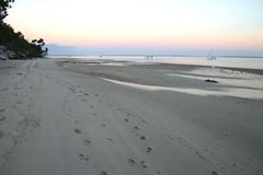 Early Morning Walk on Beach. Early morning at the beach, with footprints in the sand of people walking along the beach Stock Photo