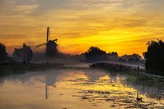Sunrise on the Dutch windmill. Early morning and warm sunrise on windmills and a canal bridge nearby Hazerswoude and Leiden, Netherlands royalty free stock images