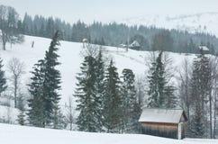 Early morning winter mountain village landscape. Jablunytsia village, Carpathian Mountains, Ukraine. Overcast windy bad weather with some blizzard royalty free stock images
