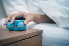 Early morning. Woman hand reaching out bed for retro alarm clock. Early morning Stock Photo