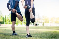Early morning workout, Fitness couple stretching outdoors in park. Young man and woman exercising together in morning, Living. Early morning workout, Fitness royalty free stock image