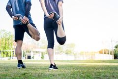 Early morning workout, Fitness couple stretching outdoors in park. Young man and woman exercising together in morning, Living royalty free stock photography