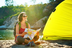 Early in the morning young woman tourist sit near the tent readi Royalty Free Stock Images