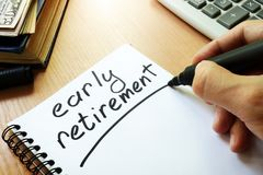 Early retirement handwritten in a note. Early retirement handwritten in a note and money Royalty Free Stock Photos