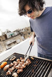 Rooftop Grillin'. Early 30's caucasian man busy grilling some meat and vegetables on the roof of a building in urban surroundings Stock Photo