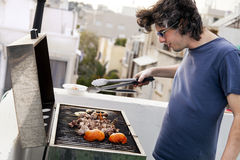 Rooftop Grillin'. Early 30's caucasian man busy grilling some meat and vegetables on the roof of a building in urban surroundings Stock Photos