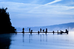 Early sport. An old jetty with peolpe doing early sport Royalty Free Stock Photo