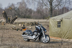 Early spring camping place. With motorcycle, big old tent and fire place with cauldron Stock Images