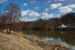 Early spring countryside. River, forest with snow remains Royalty Free Stock Photography