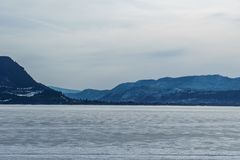 Early spring evening landscape of frozen Little Shuswap Lake British Columbia Canada. Nature snow cold forest white winter mountain blue frost ice travel stock photo