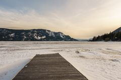 Early spring evening landscape of frozen Little Shuswap Lake British Columbia Canada. Nature snow cold forest white winter mountain blue frost ice travel royalty free stock photography