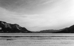 Early spring evening landscape of frozen Little Shuswap Lake British Columbia Canada black and white. Nature snow cold forest winter mountain blue frost ice royalty free stock photo