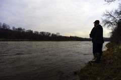 Early spring fisherman fishing off bank of fast flowing river at Royalty Free Stock Images