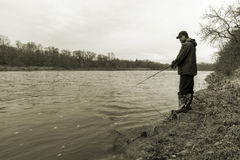 Early spring fisherman standing on the bank of a fast flowing ri Royalty Free Stock Photography