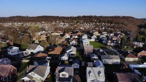 Early spring flyover of typical Pennsylvania small town neighborhood. A dusk early Spring slow forward aerial establishing shot of a typical residential stock footage