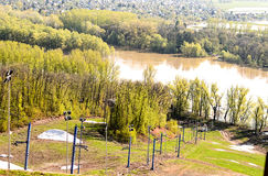 Early spring. Green trees on the bank of the river and simultaneously not melted snow royalty free stock image